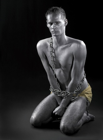 studio photography of a silver bodypainted man in chains while siting on the ground in dark back Stock Photo