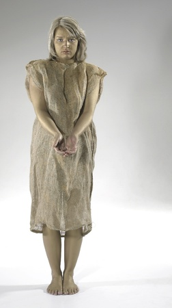 begging poor girl dressed in a gunnysack, Studio shot in light grey back photo