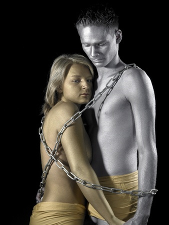 prisoner of love: studio photography of a gold and silver bodypainted couple in chains Stock Photo