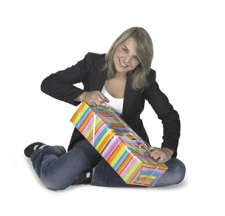 cute blond girl sitting on the ground while unwrapping a gift box, in white back Stock Photo - 11399153