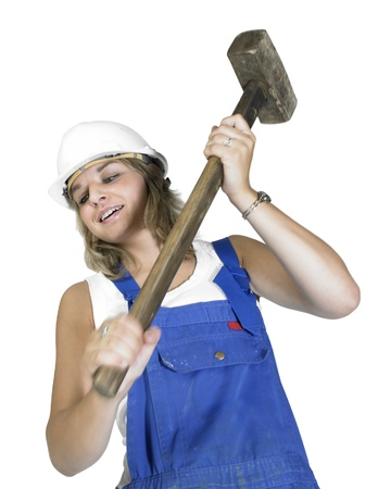 banging: Studio photography of a blond girl dressed in a blue boilersuit while banging with a sledge hammer