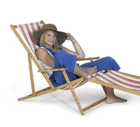 Studio shot of a blond girl relaxing in a canvas chair in white back photo