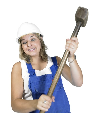 accouterment: Studio photography of a blond girl dressed in a blue boilersuit while banging with a sledge hammer