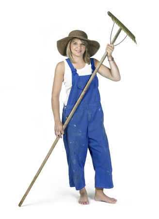 Studio photography of a blond girl dressed in a blue boilersuit holding a rake, isolated in white back photo