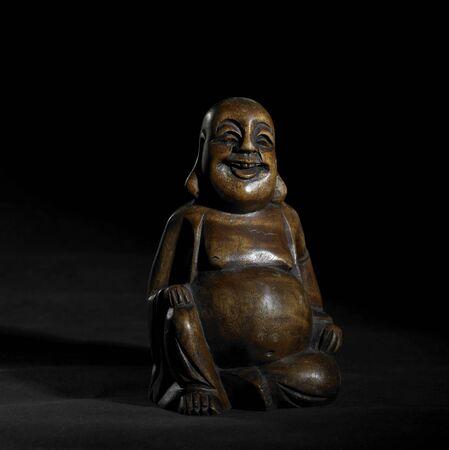 brown Buddha sculpture in dark back photo