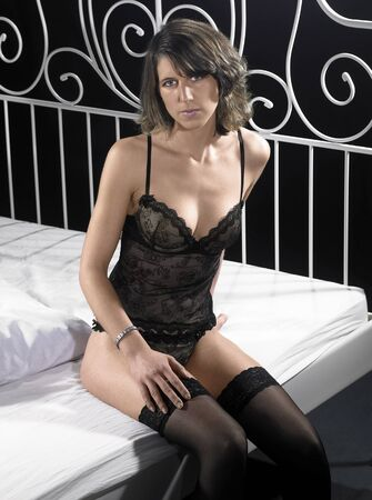 accouterment: lingerie dressed woman sitting on bed in dark back Stock Photo