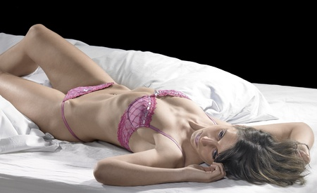 young underwear: lingerie dressed woman resting on bed in front of dark back Stock Photo