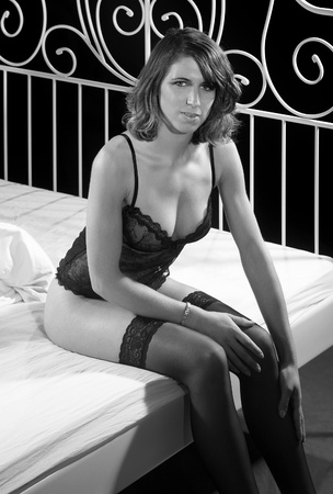 accouterment: black and white shot of a lingerie dressed woman sitting on bed in dark back