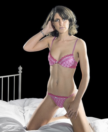 bedstead: pink lingerie dressed woman on bed in front of dark back Stock Photo