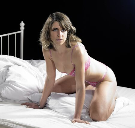 accouterment: lingerie dressed woman on bed in front of dark back