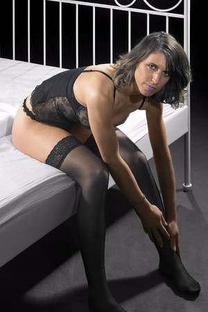 lingerie dressed woman sitting on bed in dark back photo
