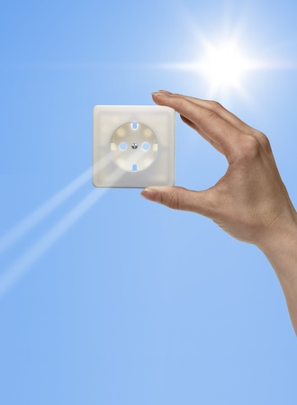 symbolic solar energy theme showing the sun and sky with human hand holding a electrical socket while sunbeams falling through Stock Photo - 12412691