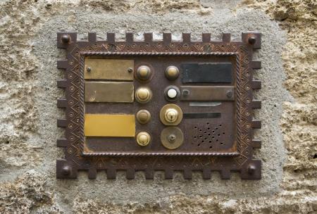 historic doorbell plate on rough facade, seen in Italy