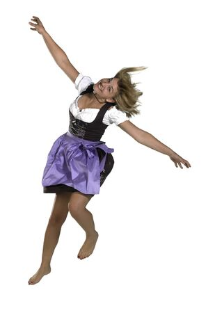 jumping blond woman wearing a traditional dress named dirndl Stock Photo