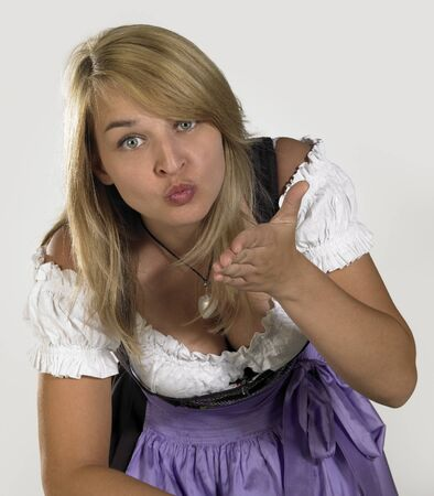 coquettish: smiling blond woman wearing a traditional dress named dirndl while blowing a kiss