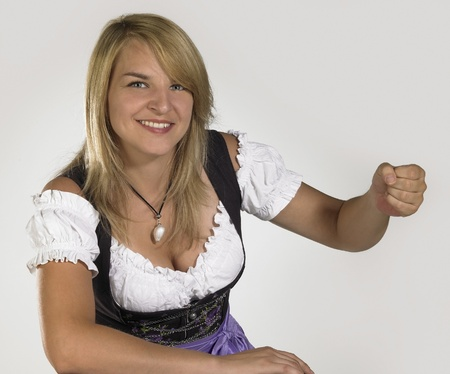 accouterment: smiling blond woman wearing a traditional dress named dirndl while holding a fictive object Stock Photo