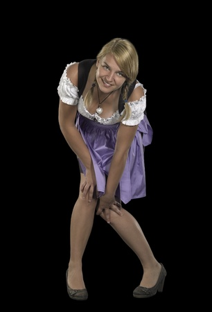 coquettish: coquettish blond woman wearing a traditional dress named dirndl in black back Stock Photo