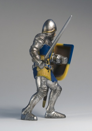 a toy knight made of plastic in grey back photo