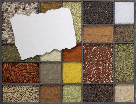 chit: lots of various different spices in a framed dark wooden box with a chit of paper on it, seen from above