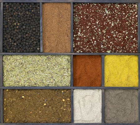 grinded: lots of various different spices in a framed dark wooden box seen from above
