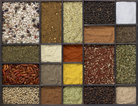 lots of various different spices in a framed dark wooden box seen from above photo