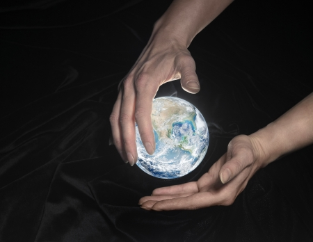 high angle shot of a shining crystal globe surrounded by black crinkly fabrics and two hands around photo