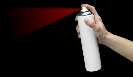 aerosol can: human hand holding a unlabeled white aerosol can with red spray in black back Stock Photo