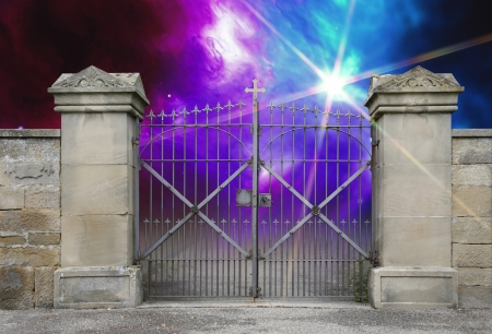reachability: entrance of a graveyard with a closed wrought-iron gate in mystic colorful ambiance Stock Photo