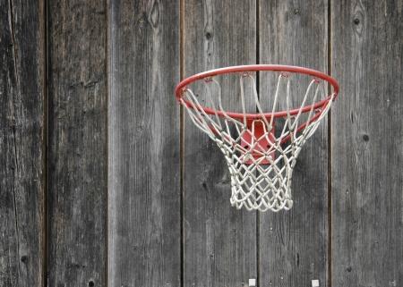 basketball hoop: a basketball basket on weathered wooden facade