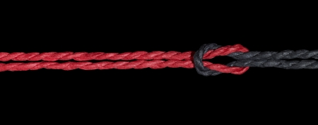 string together: a red and a black string knotted together Stock Photo