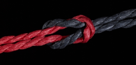 a red and a black string knotted together Stock Photo