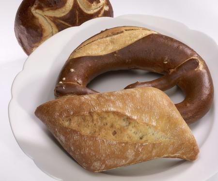 lye: german lye rolls and bread roll on a plate in light back