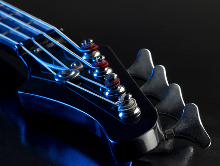 worm gear: detail of a bass guitar with blue light in black back