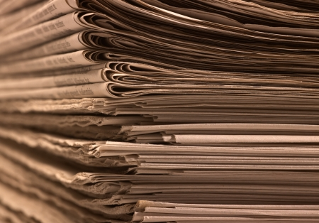 writing western: full frame background with lots of stacked newspapers, brown toned