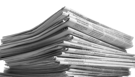 writing western: lots of stacked newspapers in light back Stock Photo