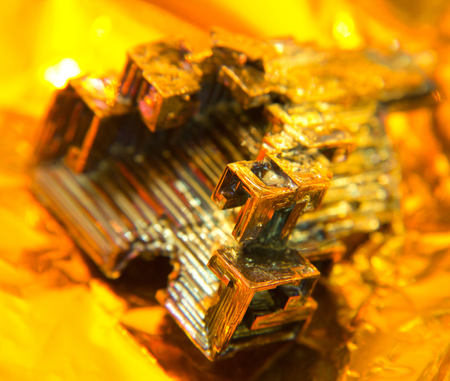 bismuth: a multicolored Bismuth crystal, warm illuminated in golden back
