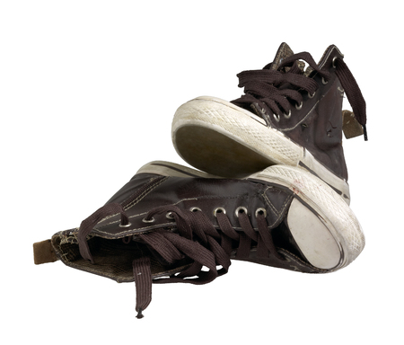 a pair of old brown sneakers in white back photo