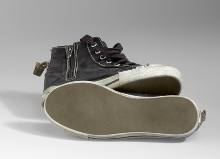 accouterment: a pair of old brown sneakers in light grey back
