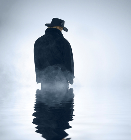 mystic scenery showing a person wearing a dark coat and hut standing in foggy ambiance with reflective water surface