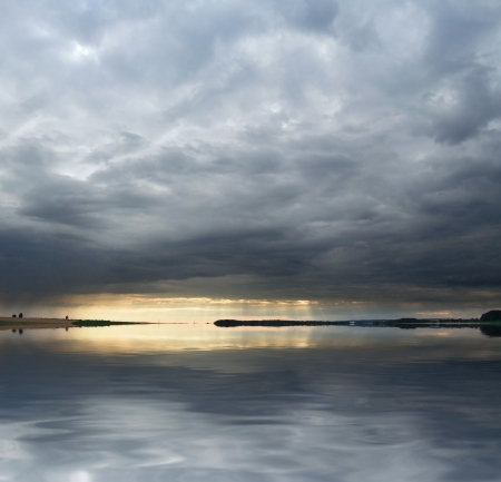 clouded stormy landscape with reflective water surface at evening time