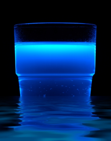 a bright blue fluorescent illuminated drink and reflective water surface in black back