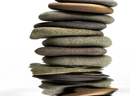 wavily: low angle view of stacked flat pebble stones and mirroring water surface in light back