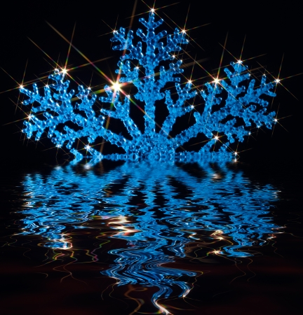 blue illuminated artificial snowflake with lots of twinkling light effects over mirroring water surface in black back