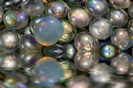 partly sunken iridescent glass beads on reflective water surface Stock Photo