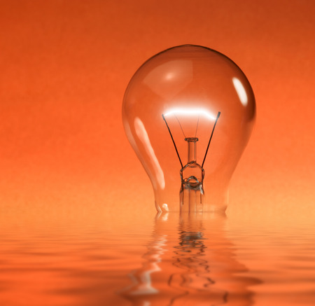 wavily: a partly sunken glowing electric light bulb on reflective water surface in orange back Stock Photo
