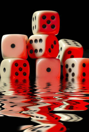 sinking pile of red illuminated white dice on reflective water surface in black back
