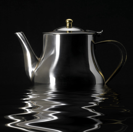wavily: sinking metallic tea pot on reflective water surface in black back Stock Photo