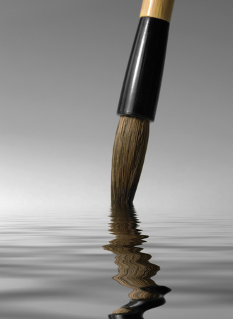 detail of a chinese brush tip dipped in a reflective water surface in grey back