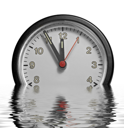 wavily: a partly sunken clock showing five minutes to twelve on reflective water surface in white back