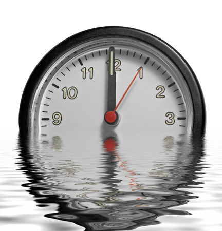 a partly sunken clock face showing past twelve o´clock on reflective water surface in white back